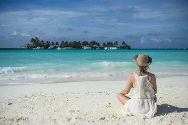 Maledives, Ari Atoll, Nalaguraidhoo, Sun Island Resort, back view of woman sitting on the beach - RUNF00730