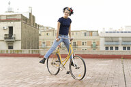 Portrait of happy young woman balancing on bicycle in the city - ERRF00427