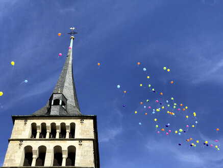 Germany, Sindelfingen, colourful wedding balloons in the sky over church spire - MABF00514