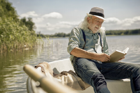 Portrait of content senior man sitting in rowing boat on a lake reading a book - VWF00017