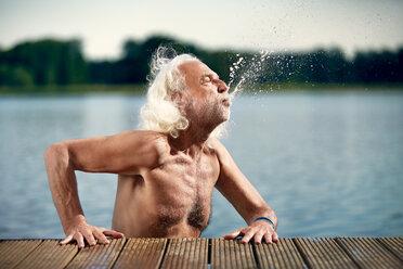 Best Ager Model, alter Mann am See, spritz Wasser aus seinem Mund am Steg am Seddinger See in Brandenburg - VWF00023