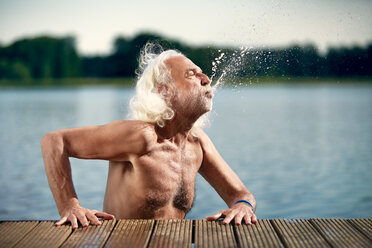 Senior man with white hair leaning on jetty splashing with water - VWF00023