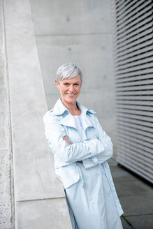 Portrait of content mature businesswoman leaning against wall wearing light blue trenchcoat - VWF00026