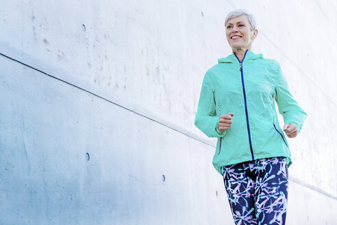 Smiling mature woman jogging along concrete wall - VWF00032
