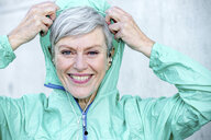 Portrait of smiling sporty mature woman putting on hood of her jacket - VWF00035