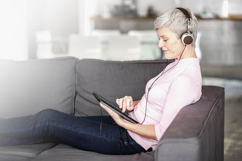 Mature woman sitting on couch using digital tablet while listening music with headphones - VWF00041