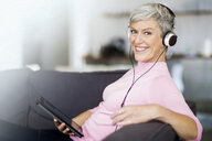 Portrait of happy mature woman sitting on couch with digital tablet listening music with headphones - VWF00044