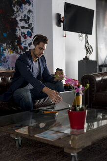 Man with headphones and takeaway coffee sitting on couch using laptop - MAU02178