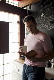 Man with cup of coffee reading a book in kitchen - MAUF02193