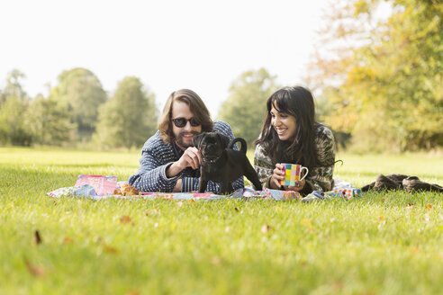 Happy young couple with puppy on picnic blanket in forest - ASTF00362