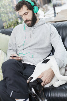 Dog lying besides man listening music on sofa at cafeteria - ASTF00419