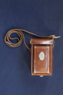 Top view of vintage camera case on blue table - ASTF00449