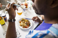 Cropped image of friends eating food at table - ASTF00536