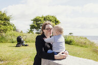 Mother with son on grassy field - ASTF00587