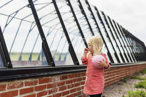 Girl holding ball while standing by glass built structure - ASTF00665