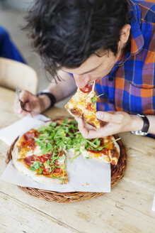 High angle view of man eating pizza at restaurant table - ASTF00686
