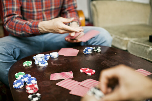 Cropped image of men playing cards at home - ASTF00782