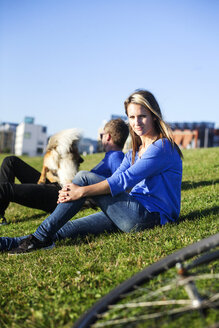 Portrait of woman sitting with man and dog in park - ASTF00830