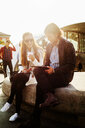 Businesswoman holding coffee cup while colleague using digital tablet outdoors - ASTF00839