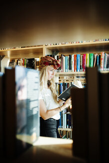 Young college student reading book in library - ASTF00869