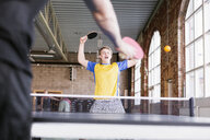 Excited teenage boy playing table tennis with friend in health club - ASTF00884