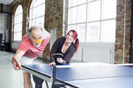 Young woman and senior man playing table tennis in health club - ASTF00887