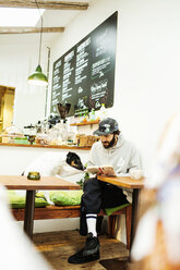 Man holding book while looking at dog in cafe - ASTF00923