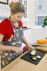 Mature woman chopping egg plant in kitchen - ASTF00935
