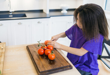 Girl slicing tomatoes in kitchen - ASTF00938