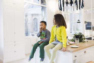 Brother and sister sitting on kitchen island - ASTF00953