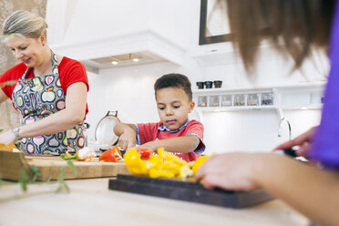 Mother with children chopping vegetables in kitchen - ASTF00959