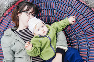 Portrait of baby girl lying with mother on round swing - ASTF01049