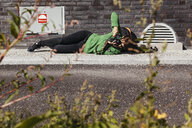 Full length of woman photographing while lying on sidewalk - ASTF01187