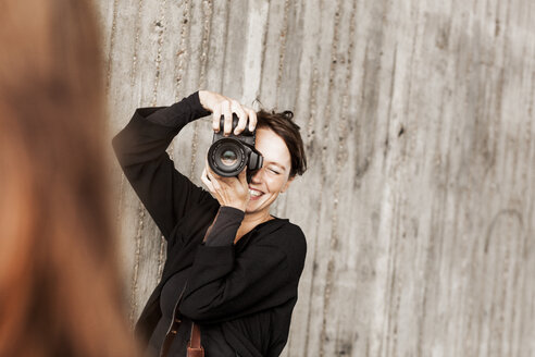 Happy woman photographing friend against wall - ASTF01193