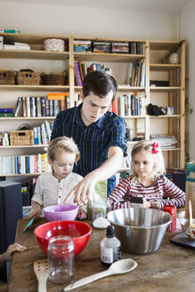 Young man guiding children in baking at home - ASTF01256