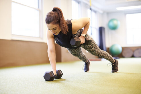 Woman doing dumbbell rows in plank position - AURF08103