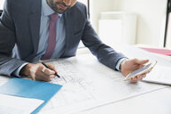Architect with cell phone reviewing blueprints - HEROF03588