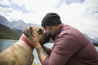 Affectionate bearded man with tattoos kissing dog at remote lakeside - HEROF03597