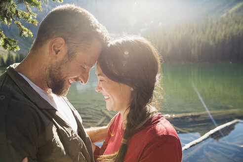 Affectionate couple laughing face to face at sunny lakeside - HEROF03600