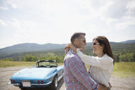 Affectionate couple hugging near convertible at rural overlook - HEROF03609