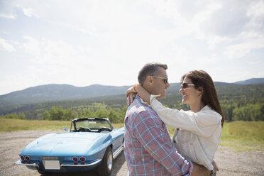 Affectionate couple hugging near convertible at rural overlook - HEROF03609