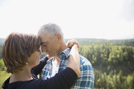 Affectionate mature couple hugging on sunny remote hilltop - HEROF03615