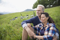 Affectionate senior couple relaxing near mountain bikes in remote rural field - HEROF03618