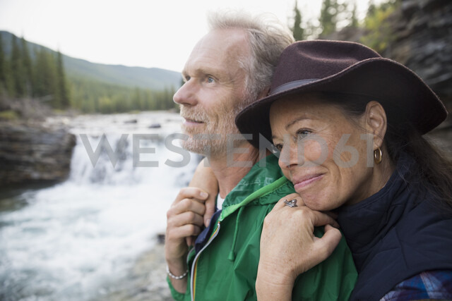 Affectionate couple hugging at waterfall - HEROF03621 - Hero Images/Westend61