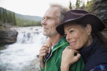 Affectionate couple hugging at waterfall - HEROF03621