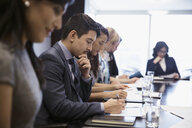 Business people reviewing paperwork in conference room meeting - HEROF03633