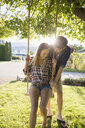 Affectionate young couple swinging at tree swing in sunny summer yard - HEROF03690