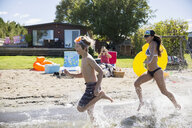 Brother and sister running and splashing in sunny summer lake - HEROF03702