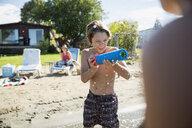 Boy playing with squirt gun at sunny summer beach - HEROF03711
