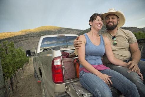 Affectionate vintner couple hugging in truck bed in vineyard - HEROF03723